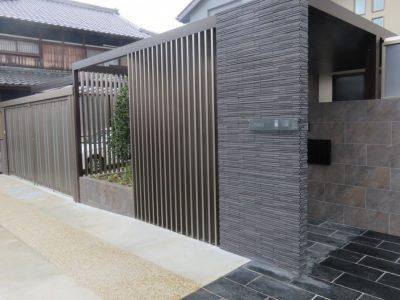 前のタイル貼りの塀がサイン設置の門柱。 門扉はこの塀の奥に隠されています。→